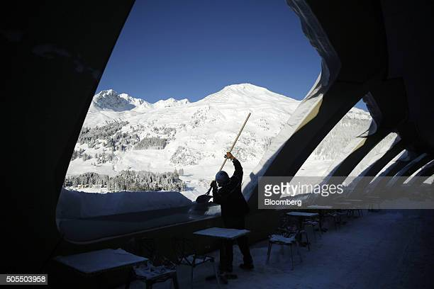 A hotel employee uses a snow shovel to clear snow from the balconies of 10th floor bar terrace at the InterContinental Hotel Davos operated by...