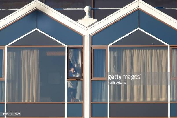 Hotel guest looks out of a window at the Radisson Blu hotel, Heathrow Airport, where travellers are completing their quarantine period on February...