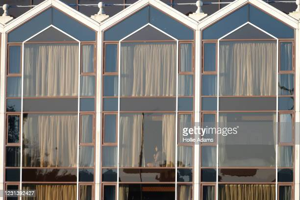 Hotel guest sits on a window sill at the Radisson Blu hotel near Heathrow Airport where travellers are completing their quarantine period on February...