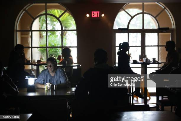 Hotel guests eat breakfast by lamplight after the Courtyard by Marriott was left without power by Hurricane Irma September 10 2017 in Fort Lauderdale...