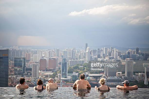 Hotel guests in the infinity pool at the SkyPark atop Marina Bay Sands look out towards the city skyline in Singapore on Tuesday Feb 28 2012 The...