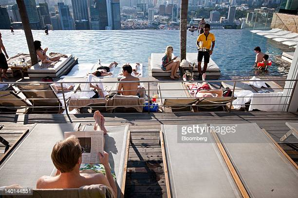 Hotel guests lay by the infinity pool at the SkyPark atop Marina Bay Sands in Singapore on Tuesday Feb 28 2012 The number of visitors to the island...