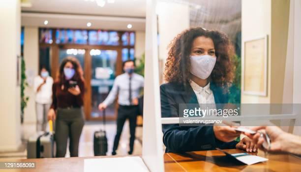 hotelgäste mit schützenden gesichtsmasken und sozialer entsagung vor der hotelrezeption - gast stock-fotos und bilder