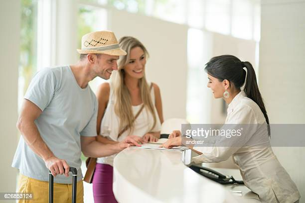 hotel hostess helping couple with the check-in - hotel stock pictures, royalty-free photos & images