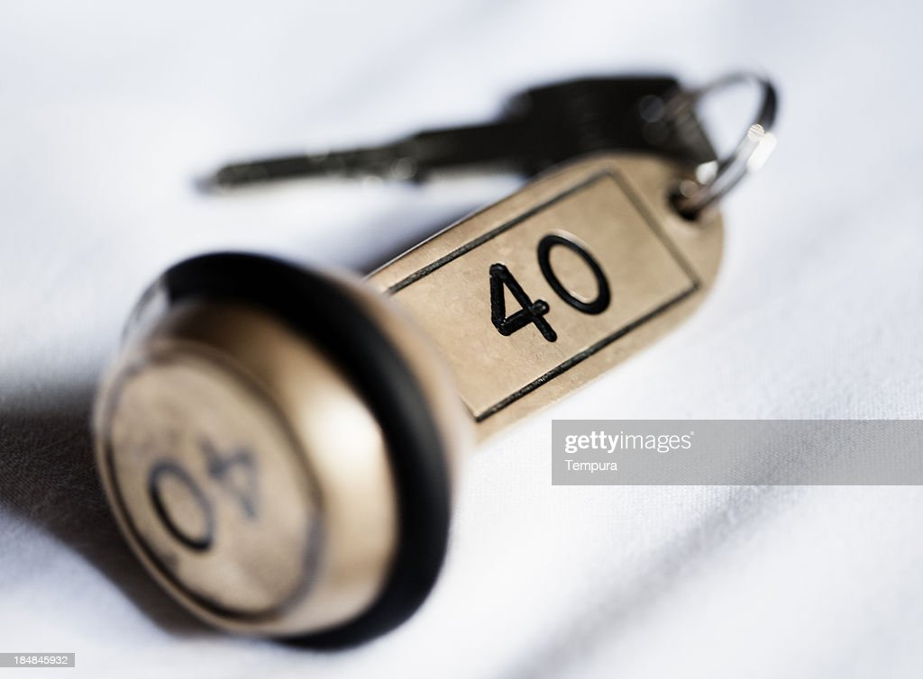Hotel key lying on the room's bed. : Stock Photo
