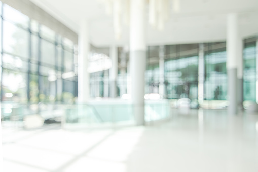 Hotel lobby blur background banquet hall interior view of luxurious foyer of empty atrium space and entrance doors and glass wall 990877026