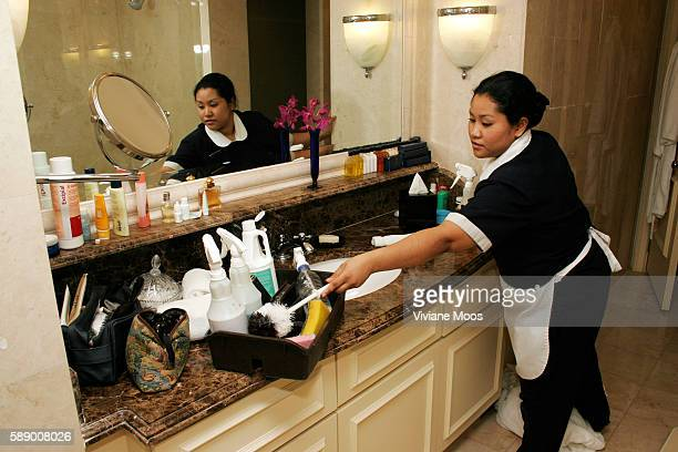 Hotel maid cleans the bathroom of a guest room