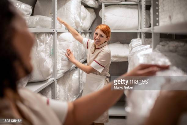 hotel maids picking up clean bedding and towels - hotel stock pictures, royalty-free photos & images