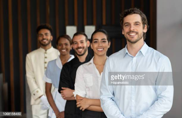 hotel manager and his team standing behind all looking at camera smiling - hotel stock pictures, royalty-free photos & images