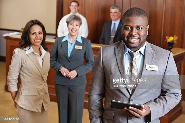 Hotel manager holding tablet with service team