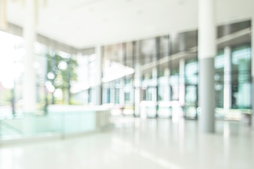 Hotel or office lobby blur background interior view toward reception hall, modern luxury white room space with blurry corridor and building glass wall window 1156171081