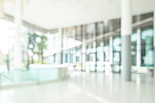 Hotel or office lobby blur background interior view toward reception hall, modern luxury white room space with blurry corridor and building glass wall window