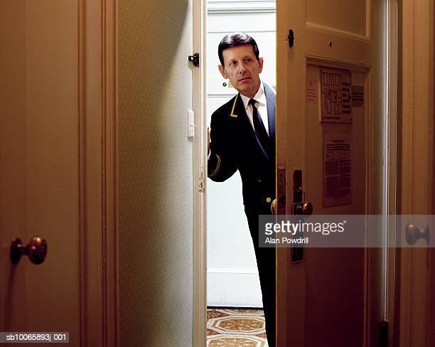Hotel porter looking around door