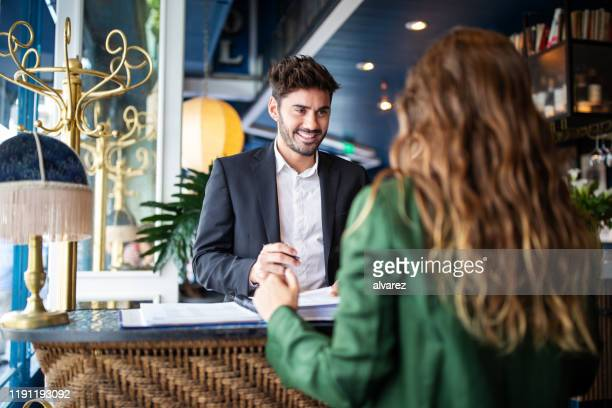 hotel receptionist assisting guest for checking in - hotel stock pictures, royalty-free photos & images
