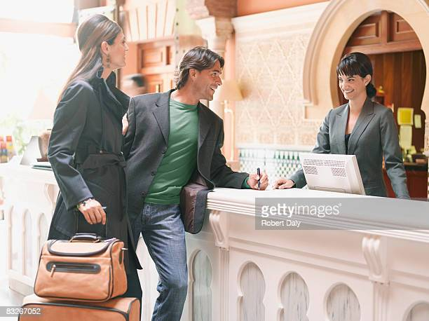 Hotel receptionist checking couple in