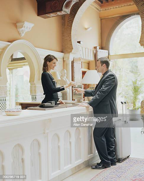 hotel receptionist greeting businessman, handing key over desk - hotel key stock photos and pictures