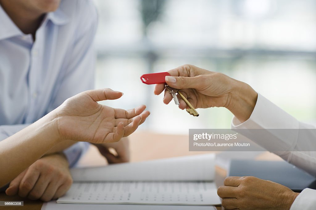 Hotel receptionist handing room key to guest : Stock Photo