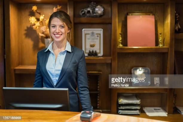 hotelrezeptionist lächelnd in die kamera - uniform stock-fotos und bilder