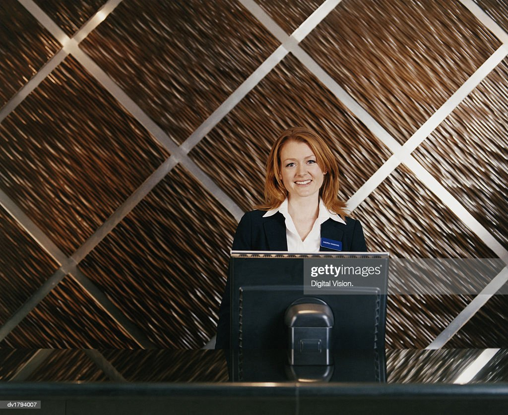 Hotel receptionist stands behind a computer monitor on a reception hotel receptionist stands behind a computer monitor on a reception desk stock photo sciox Images