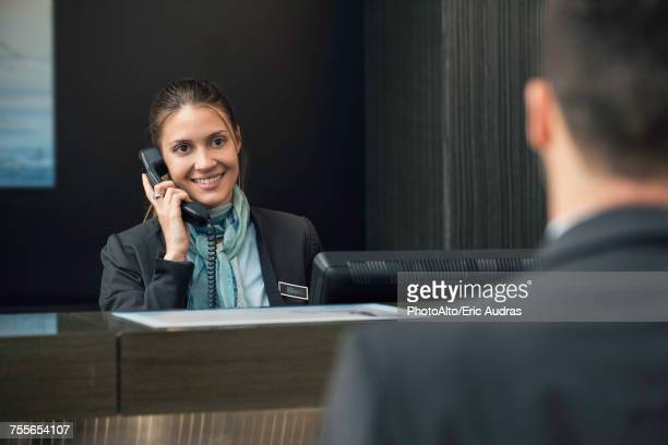 Hotel receptionist talking on phone