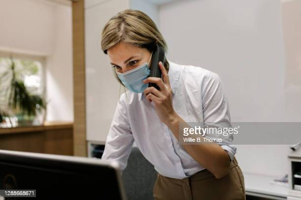hotel receptionist talking on phone while wearing face mask - germany stock pictures, royalty-free photos & images