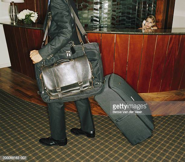 Hotel receptionist watching man depart with luggage