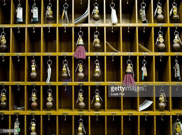 Hotel room keys in pigeon holes behind reception desk
