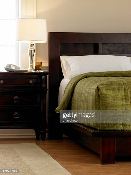 Hotel room with dark wood furniture and green bedding