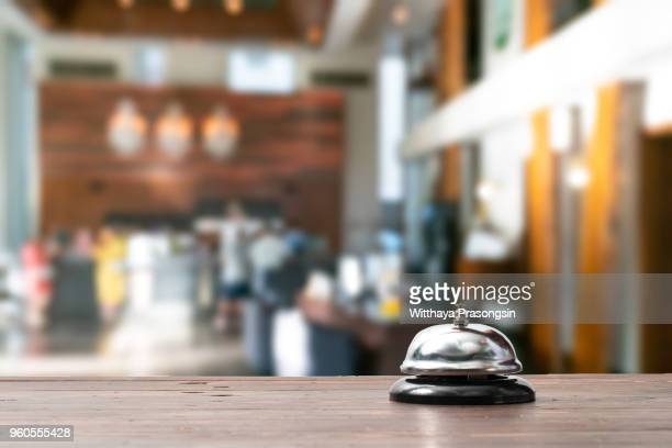 "Hotel service bell on a table white glass and simulation hotel background. Concept hotel, travel, room""n"