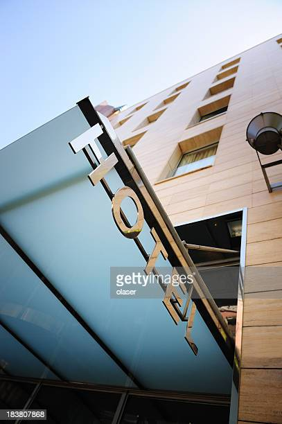 hotel sign over building entrance - entrance sign stock photos and pictures