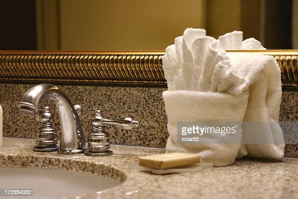 hotel sink with towels, mirror, soap and faucet - grooming product stock photos and pictures