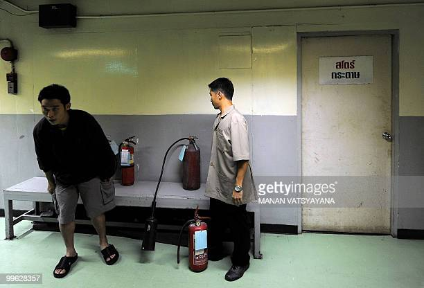 Hotel staff arrange fire extinguishers in the basement of the Dusit Thani hotel after evacuating following an explosion and gunfire were heard around...
