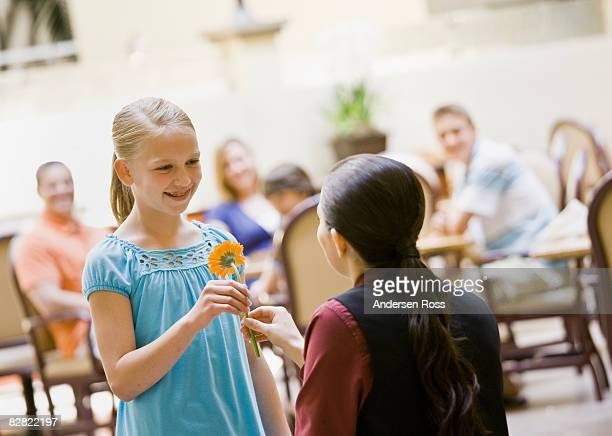 Hotel staff handing a young girl a flower