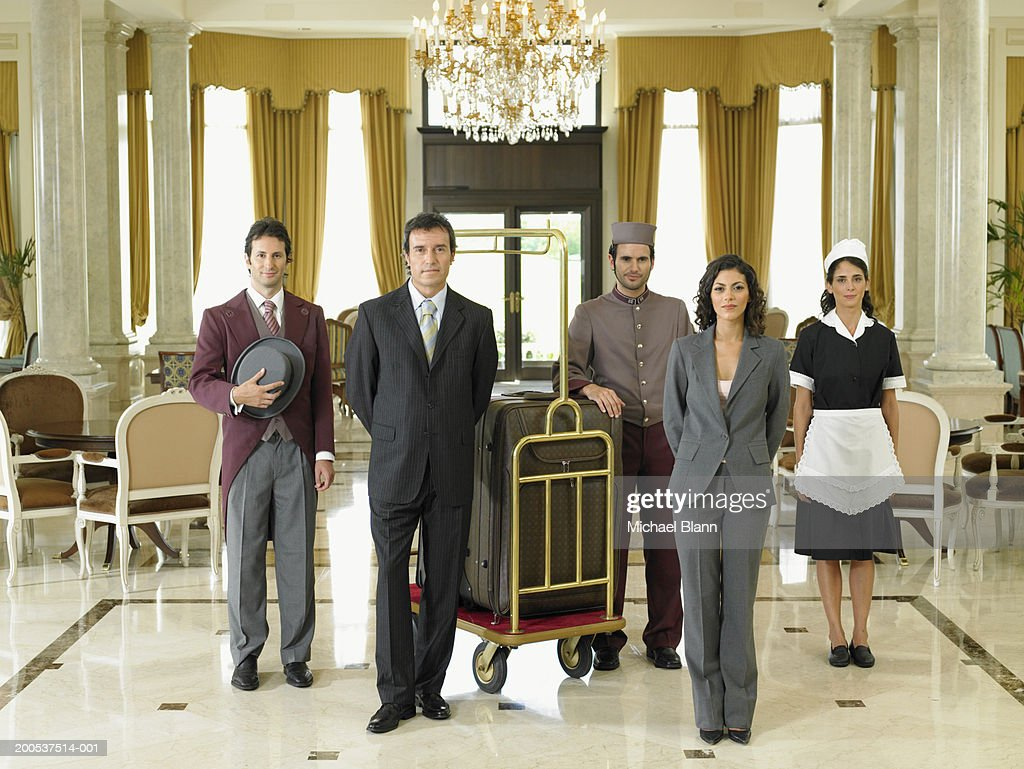Hotel staff standing in foyer, portrait : Stock Photo