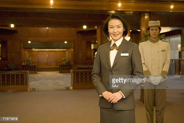 Hotel staffs, reception desk in background, smiling, portrait, front view