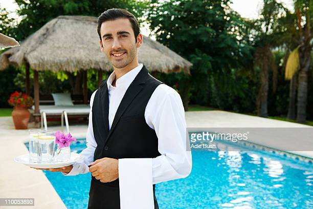 Hotel waiter holding tray by hotel pool