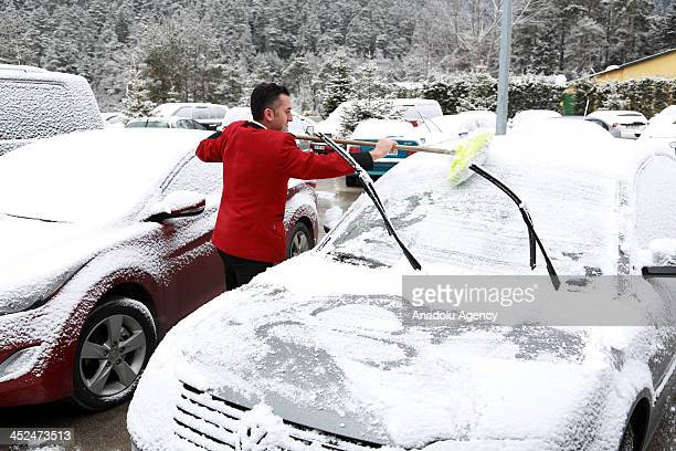 A hotel worker cleans the snow over the visitors' cars at snow covered Abant Nature Park on November 29 2013 in Bolu Turkey