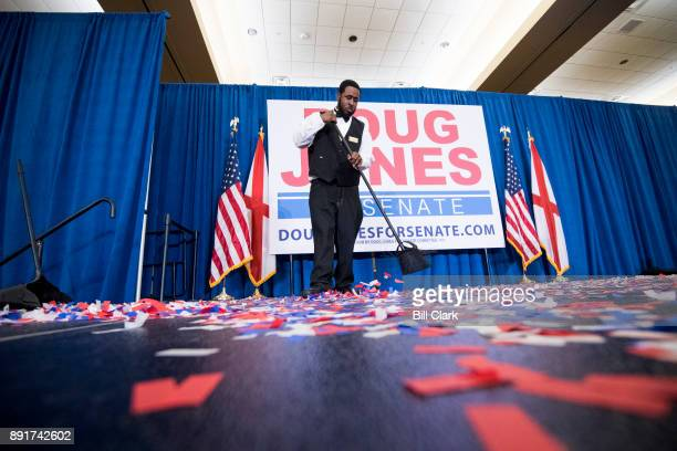 A hotel worker sweeps up confetti on stage after the election night victory party for Alabama Democrat Doug Jones at the Sheraton in Birmingham Ala...
