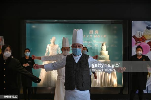 TOPSHOT Hotel workers wearing protective masks exercise in the lobby during a staff briefing about how to implement new regulations concerning the...