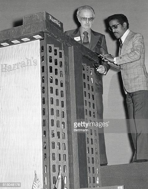 Hotel-casino owne, Bill Harrah and Sammy Davis, Jr., shake hands in front of a huge cake replica of Harrah's Tahoe Hotel-Casino. Davis was master of...