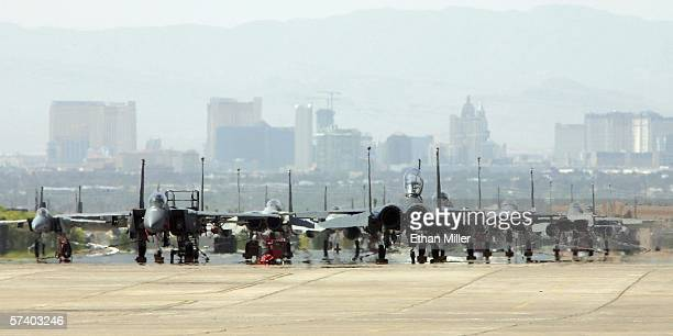 Hotelcasinos on the Las Vegas Strip are seen behind fan aircraft lined up on the flight line at Nellis Air Force Base during the Joint Expeditionary...
