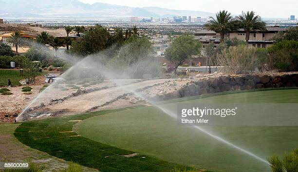 Hotel-casinos on the Las Vegas Strip are seen behind sprinklers watering the golf course at DragonRidge Country Club June 19, 2009 in Henderson,...