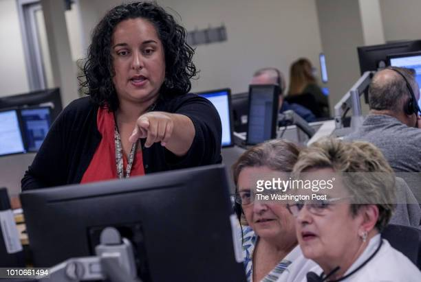 Hotline agent Jessica Coates standing works with colleagues Ilene Patterson and Pat Heck at the White House VA Hotline in Shepherdstown WV on July 27...