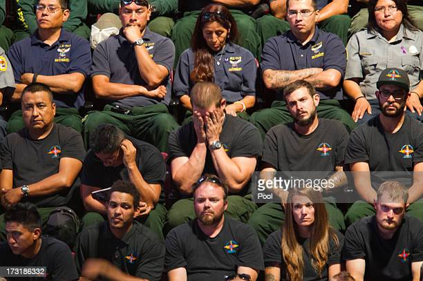 Hotshot crews look on during a memorial service honoring 19 fallen firefighters at Tim's Toyota Center July 9 2013 in Prescott Valley Arizona The 19...