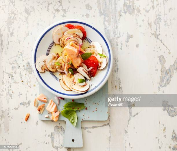 Hot-smoked salmon with champignons, onion, cherry tomatoes, almonds and olive oil