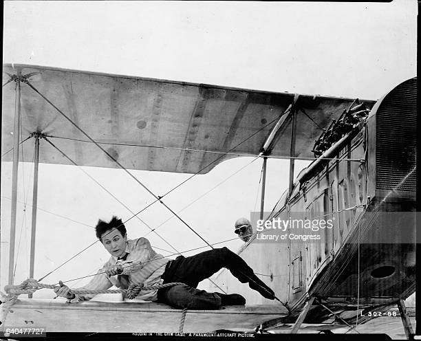 Houdini lies on the wing of a biplane holding on to the wires and a rope in the movie The Grim Game