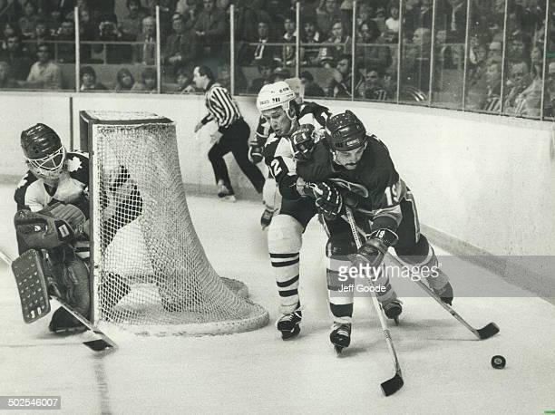 Hounding Trottier Laurie Boschman of the Toronto Maple Leafs badgers Bryan Trottier as the Islander centre tries to get control of puck behind the...