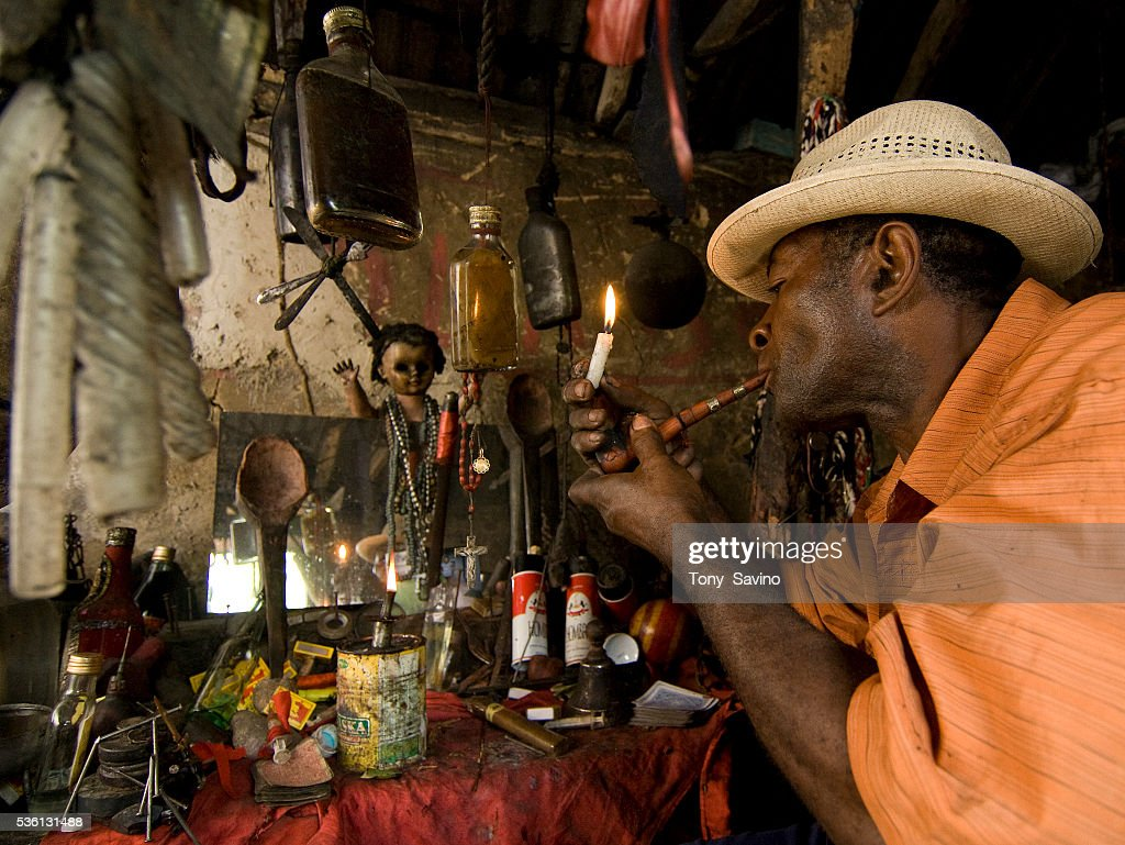 A houngan, or voodoo priest, lights a pipe in his peristil