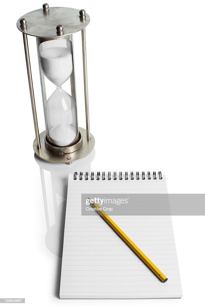 Hour glass, pencil and writing pad : Stock Photo