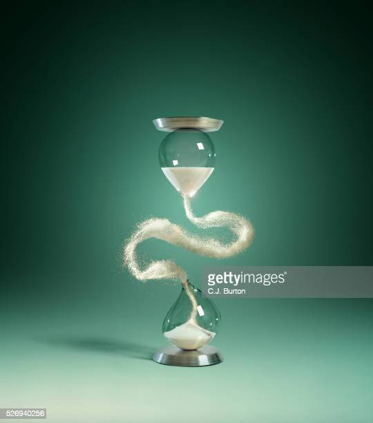 hour glass with floating sand - ampulheta imagens e fotografias de stock